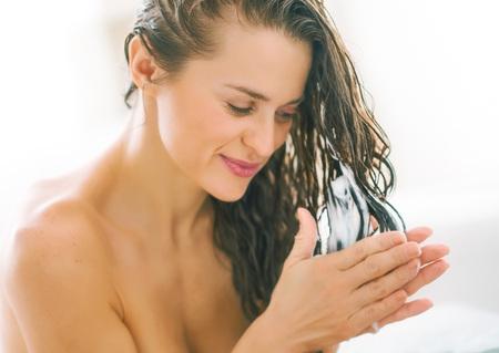 modern bathroom: Happy young woman applying hair conditioner in bathtub
