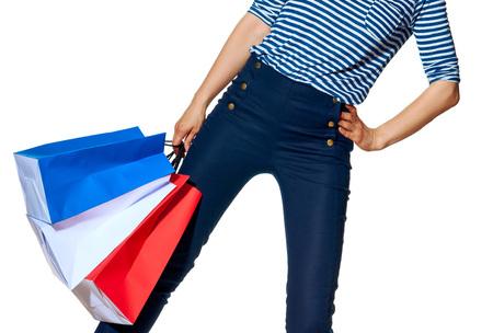 Boodschappen doen. De Franse manier. Close-up op gelukkige moderne mode-monger holding boodschappentassen van de kleuren van de Franse vlag geïsoleerd op een witte achtergrond