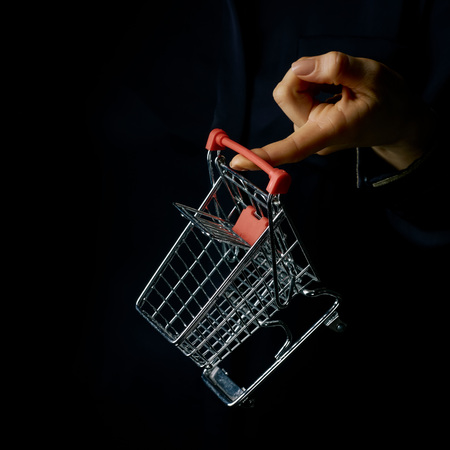 Black Mania. woman hand isolated on black showing mall shopping cart