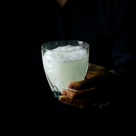 Black Mania. woman hand isolated on black background showing glass of water with effervescent tablet