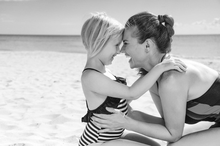 Sun kissed beauty. happy healthy mother and child in swimsuit on the seacoast embracing