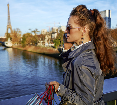 Get your bags ready for the Paris autumn sales. young trendy woman in sunglasses with shopping bags speaking on a cell phone in the front of Eiffel tower Stock Photo