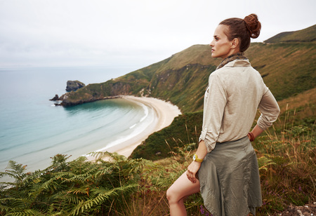 Into the wild in Spain. adventure woman hiker looking into the distance in front of ocean view landscape