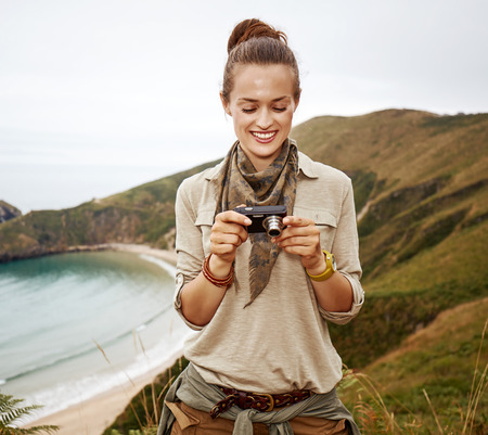 Into the wild in Spain. smiling adventure woman hiker viewing photos on camera in front of ocean view landscape 版權商用圖片