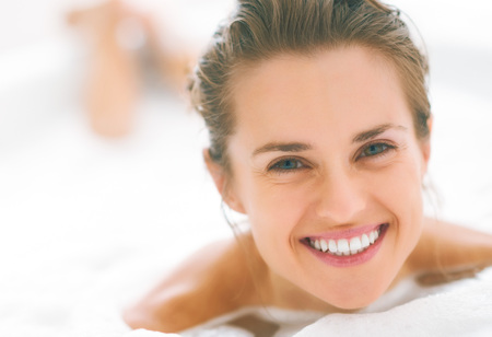 smiling young woman laying in bathtub Stock Photo