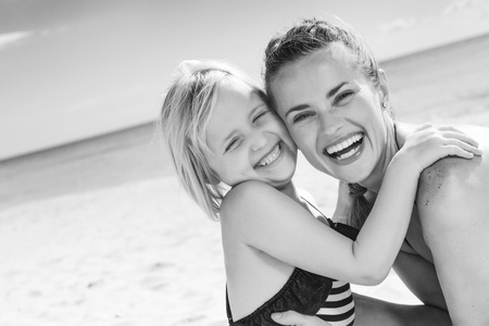 Sun kissed beauty. smiling healthy mother and daughter in beachwear on the seashore embracing