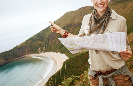 Into the wild in Spain. smiling healthy woman hiker holding map and pointing in front of ocean view landscape