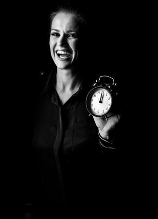 ? Wegwezen in het licht. Portret van glimlachende vrouw in de donkere die kleding op zwarte wordt geïsoleerd die wekker tonen Stockfoto