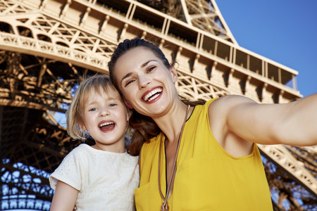 Touristy, without doubt, but yet so fun. Portrait of smiling mother and child taking selfie in the front of Eiffel tower in Paris, France Stok Fotoğraf