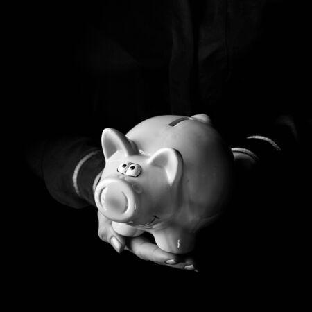 블랙 매니아. 여자 손을 돼지 저금통을 게재하는 검은 배경에 고립 스톡 콘텐츠 - 83771422