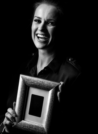 ?oming out into the light. Portrait of smiling woman in the dark dress isolated on black background showing a photo frame