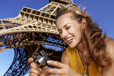 Touristy, without doubt, but yet so fun. happy young woman viewing photos on camera in the front of Eiffel tower in Paris, France