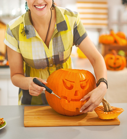Frightful Treats on the way. Closeup on smiling modern housewife in the Halloween decorated kitchen carving a big orange pumpkin Jack-O-Lantern