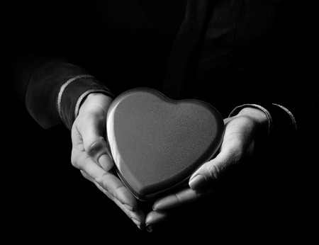shaped: Black Mania. woman hands isolated on black showing heart shaped candy box