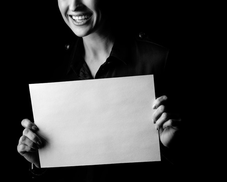 ?oming out into the light. Closeup on smiling woman in the dark dress isolated on black background showing blank paper sheet Stock Photo