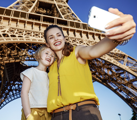 Touristy, without doubt, but yet so fun. happy mother and child tourists taking selfie with smartphone against Eiffel tower in Paris, France