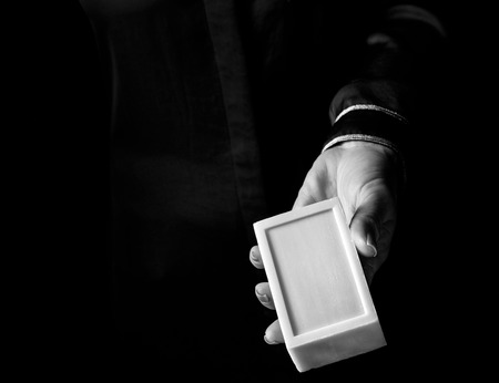 Black Mania. woman hand isolated on black showing a bar of soap Stock Photo