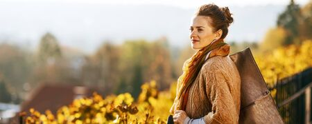 Young woman in autumn outdoors looking into distance