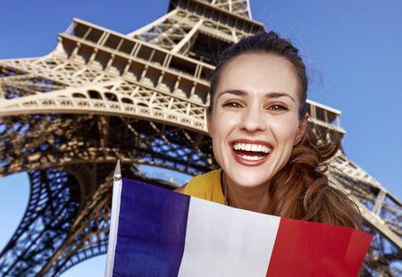Touristy, 의심의 여지가 있지만, 아직 재미. 프랑스 파리에서에서 에펠 탑에 대 한 플래그를 게재하는 젊은 여자의 미소의 초상화 스톡 콘텐츠