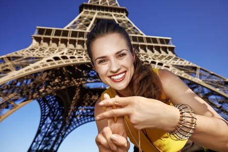 Touristy, 의심의 여지가 있지만, 아직 재미. 파리, 프랑스의 에펠 탑에 대하여 해시 태그 제스처를 보여주는 젊은여자가 미소