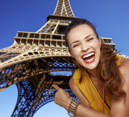 touristy: Touristy, without doubt, but yet so fun. Portrait of happy young woman pointing on Eiffel tower in Paris, France Stock Photo