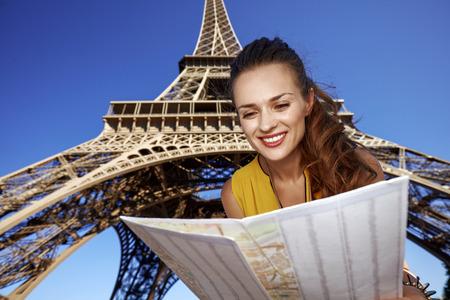 Touristy, 의심의 여지가 있지만, 아직 재미. 파리, 프랑스에 에펠 타워의 앞에 관광 명소를 탐색하는 행복 한 젊은 여자의 초상화