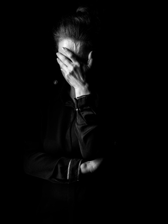 ?oming out into the light. Portrait of stressed woman in the dark dress isolated on black background Stock Photo