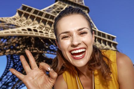 Touristy, 의심의 여지가 있지만, 아직 재미. 파리, 프랑스에서 에펠 타워의 앞에 확인 제스처를 게재하는 젊은 여자의 미소의 초상화
