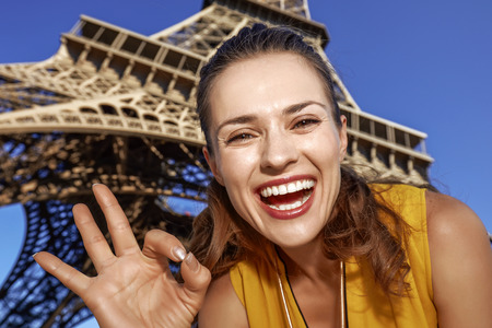 Touristy, without doubt, but yet so fun. Portrait of smiling young woman showing ok gesture in the front of Eiffel tower in Paris, France