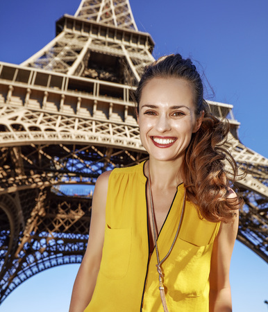 Touristy, without doubt, but yet so fun. Portrait of happy young woman against Eiffel tower in Paris, France Фото со стока