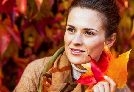 가을의 사려 깊은 젊은 여자의 초상화 leafs 단풍 앞의