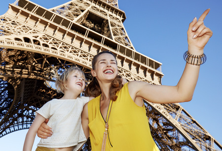 Touristy, without doubt, but yet so fun. happy mother and daughter pointing on something in the front of Eiffel tower in Paris, France Stok Fotoğraf