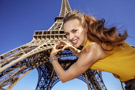 Touristy, 의심의 여지가 있지만, 아직 재미. 프랑스 파리에서에서 에펠 탑에 대 한 손 모양의 심장을 보여주는 젊은여자가 미소 스톡 콘텐츠