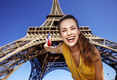 Touristy, 의심의 여지가 있지만, 아직 재미. 행복 한 젊은 여자 상승 파리, 프랑스에서 에펠 탑에 대 한 플래그의 초상화 스톡 콘텐츠
