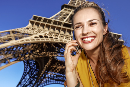 Touristy, without doubt, but yet so fun. happy young woman using a cell phone against Eiffel tower in Paris, France