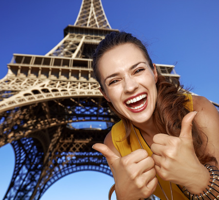 Touristy, without doubt, but yet so fun. Portrait of smiling young woman showing thumbs up in the front of Eiffel tower in Paris, France