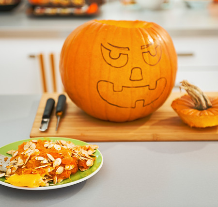 Frightful Treats on the way. Closeup on pumpkin seeds on the plate in the Halloween decorated kitchen with big pumpkin Jack-O-Lantern in background Stock Photo