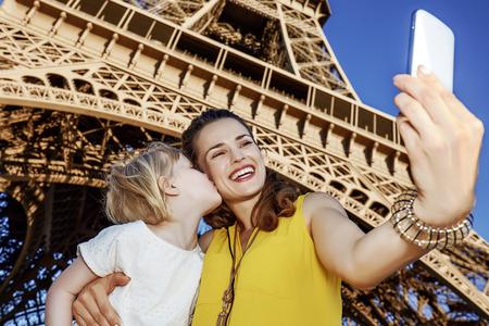 Touristy, 의심의 여지가 있지만, 아직 재미. 해피 어머니와 딸 관광객 파리, 프랑스에서 에펠 타워의 앞에 스마트 폰와 셀 꾸 얼굴을 복용 스톡 콘텐츠