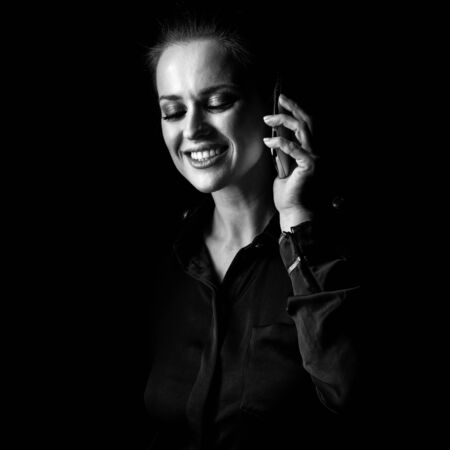 ?oming out into the light. Portrait of happy woman in the dark dress isolated on black background using a cell phone Stock Photo
