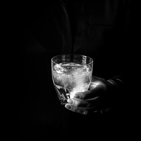 Zwarte Manie. Vrouwelijke hand geïsoleerd op zwarte achtergrond met glas water met bruisende tablet Stockfoto - 83771995