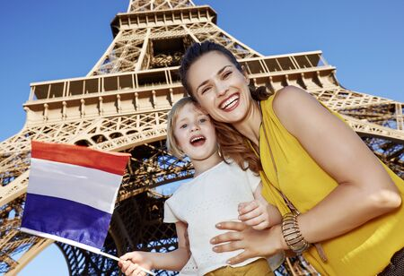 Touristy, without doubt, but yet so fun. happy mother and daughter travellers showing flag against Eiffel tower in Paris, France