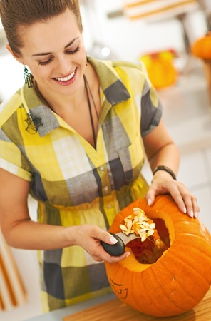 Frightful Treats on the way. happy young woman in the Halloween decorated kitchen prepare big orange pumpkin for carving