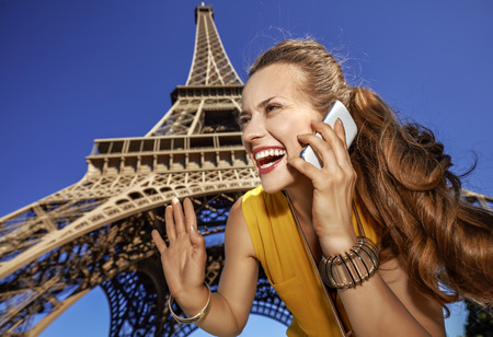 Touristy, without doubt, but yet so fun. smiling young woman speaking on a cell phone and hand waving against Eiffel tower in Paris, France Stok Fotoğraf