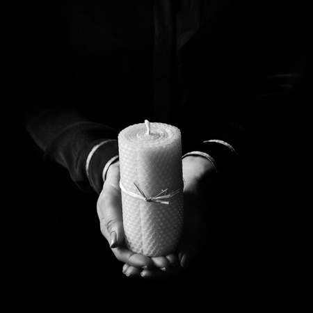 Black Mania. female hands isolated on black background showing a candle Banco de Imagens