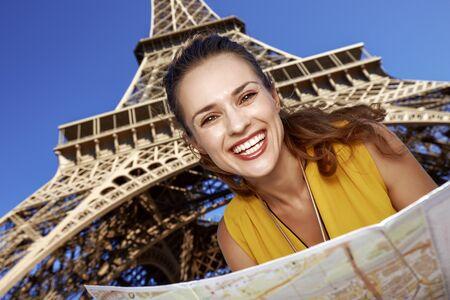 Touristy, 의심의 여지가 있지만, 아직 재미. 파리, 프랑스에서 에펠 타워에 대 한지도 함께 행복 한 젊은 여자
