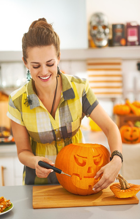 Frightful Treats on the way. happy young housewife in the Halloween decorated kitchen carving a big orange pumpkin Jack-O-Lantern