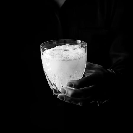 Zwarte Manie. Vrouwelijke hand geïsoleerd op zwarte achtergrond met glas water met bruisende tablet Stockfoto - 83771490