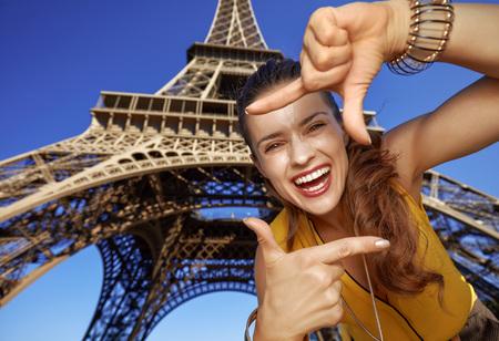Touristy, 의심의 여지가 있지만, 아직 재미. 파리, 프랑스에서 에펠 타워에 대하여 손으로 프레이밍 웃는 젊은 여자의 초상화 스톡 콘텐츠