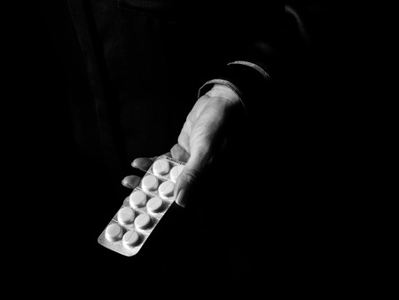 Zwarte Manie. Vrouwelijke hand geïsoleerd op zwarte achtergrond met pak pillen