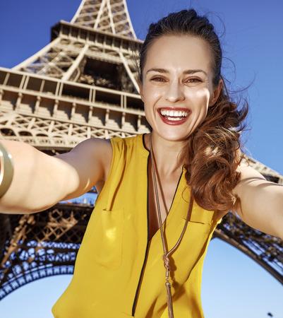 Touristy, 의심의 여지가 있지만, 아직 재미. 파리, 프랑스에서 에펠 탑에 대하여 셀리를 복용하는 행복 한 젊은 여자